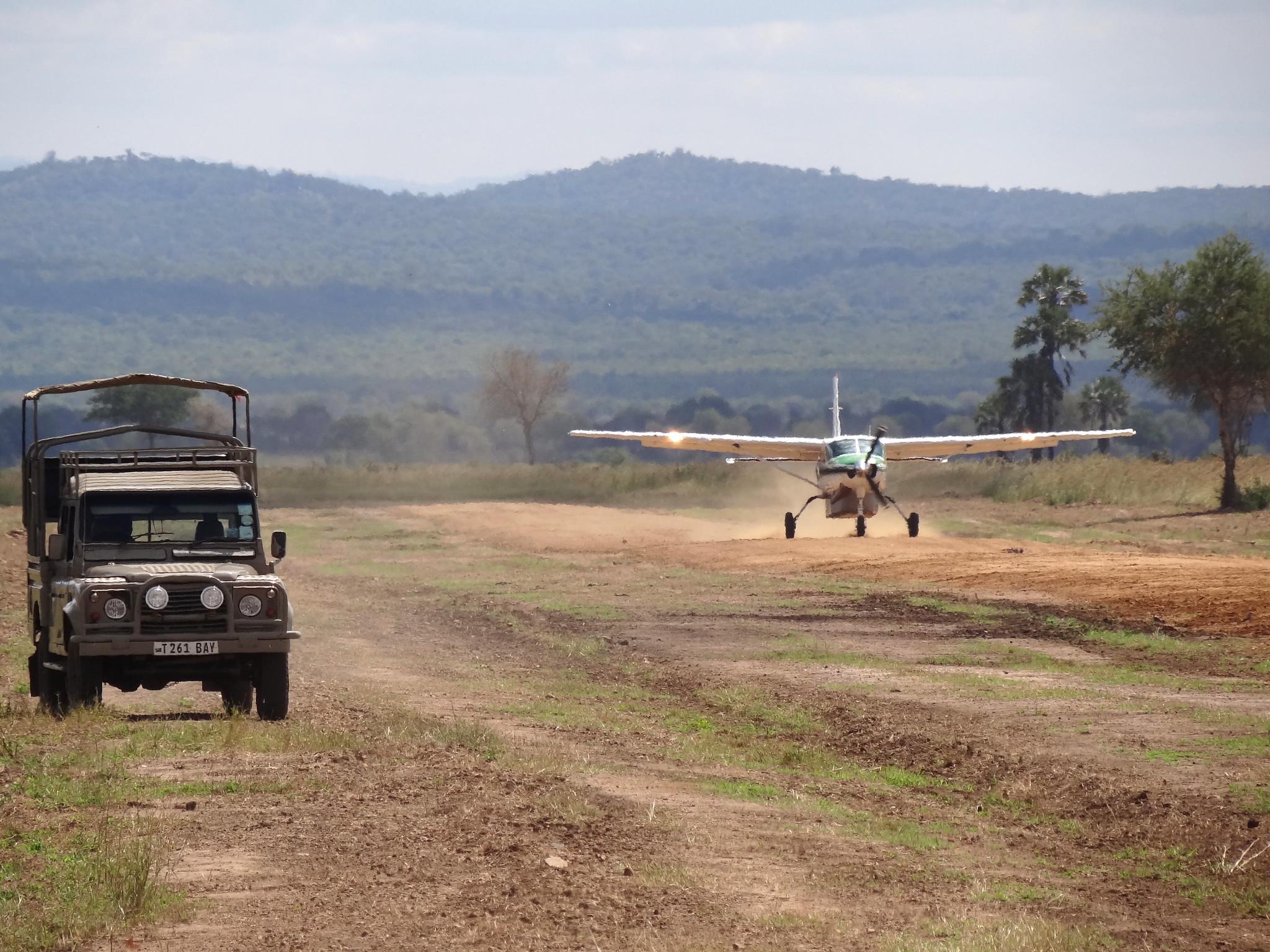 A Cessna landing alongside a Land Rover in Mikumi National Park, Tanzania. Photograph by Adam Jones, 2013. CC BY-SA 2.0.